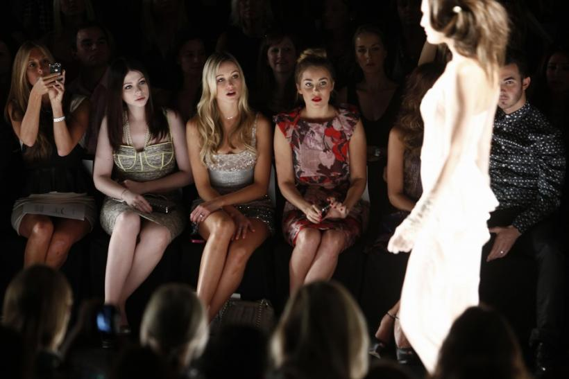 Actresses Michelle Trachtenberg (2nd L), Katrina Bowden (3rd L) and television personality Lauren Conrad (4th L) watch the Badgley Mischka Spring/Summer 2013 collection show at New York Fashion Week September 11, 2012.