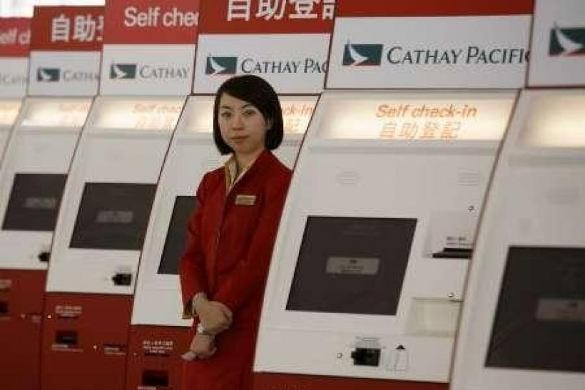 A Cathay Pacific attendant waits for customers beside a column of self check-in machines at the Hong Kong airport.
