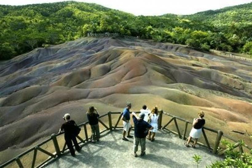 Tourists survey the unusual natural phenomena of the seven-coloured earth at Chamarel in west Mauritius