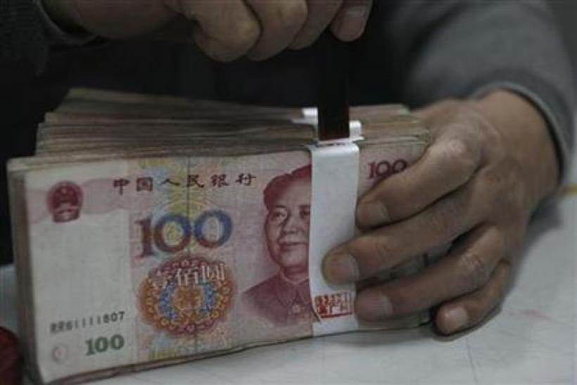An employee seals a stack of yuan banknotes at a branch of Industrial and Commercial Bank of China in Huaibei