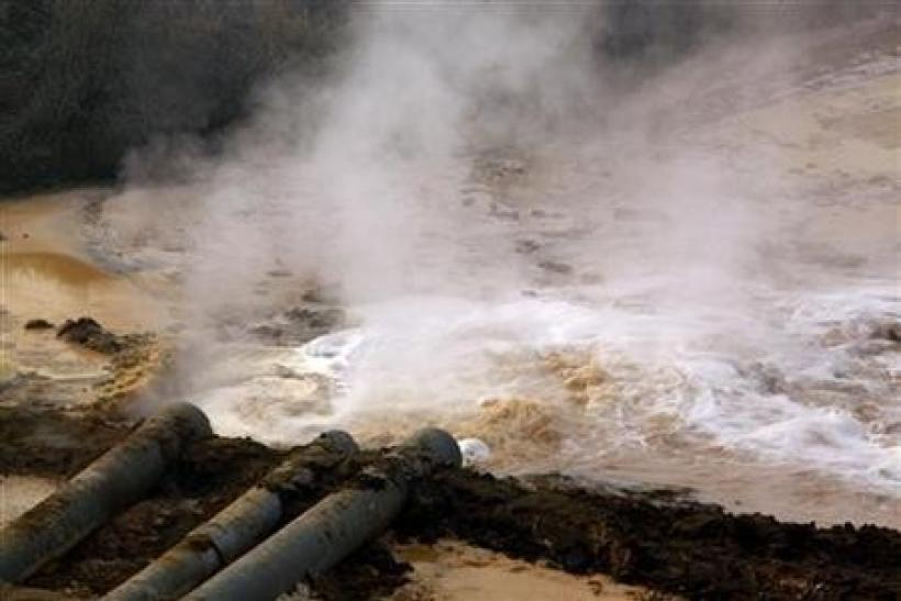 Pipes coming from a rare earth smelting plant spew polluted water into a vast tailings dam near Xinguang Village