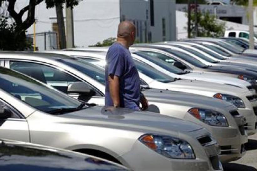 A man walks next to Chevrolet vehicles at a GM dealership in Miami