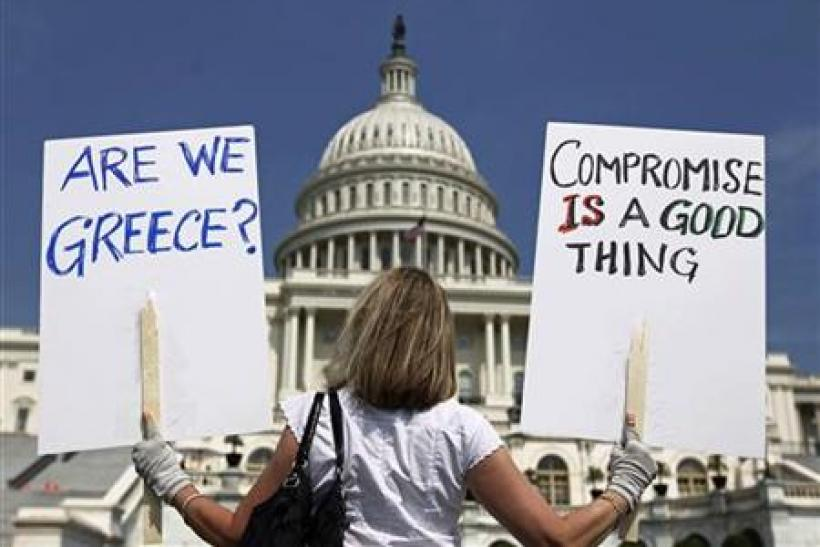 A demonstrator holds placards to protest U.S. debt in front of the Capitol in Washington July 18, 2011. REUTERS/Kevin Lamarque