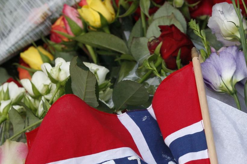 A Norwegian national flag is seen among flowers to mourn the victims of a shooting spree on an island in the countryside and a bomb attack in the capital Oslo