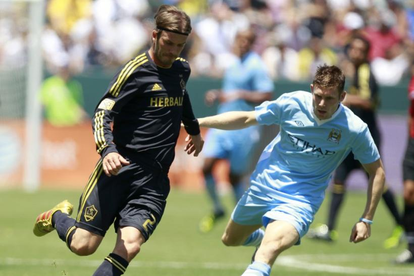 Los Angeles Galaxy's David Beckham (L) controls the ball in front of Manchester City's James Milner during their World Football Challenge soccer match in Carson, California