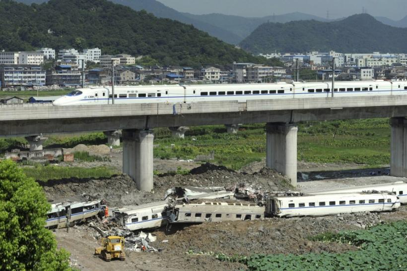 A high speed bullet train runs past a railway bridge past carriage wreckage (below) after two trains crashed and derailed in Wenzhou, Zhejiang province July 25, 2011. China sacked three senior railway officials on Sunday after a collision between two high