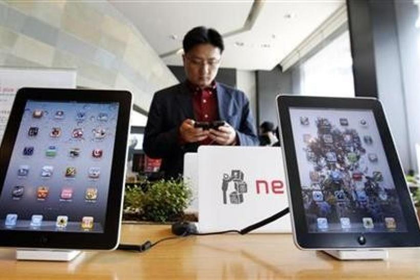 A customer holds a Apple Inc iPhone 4 smartphone on display behind the company's iPad tablets at a registration desk at the headquarters of South Korean mobile carrier KT in Seoul April 19, 2011.