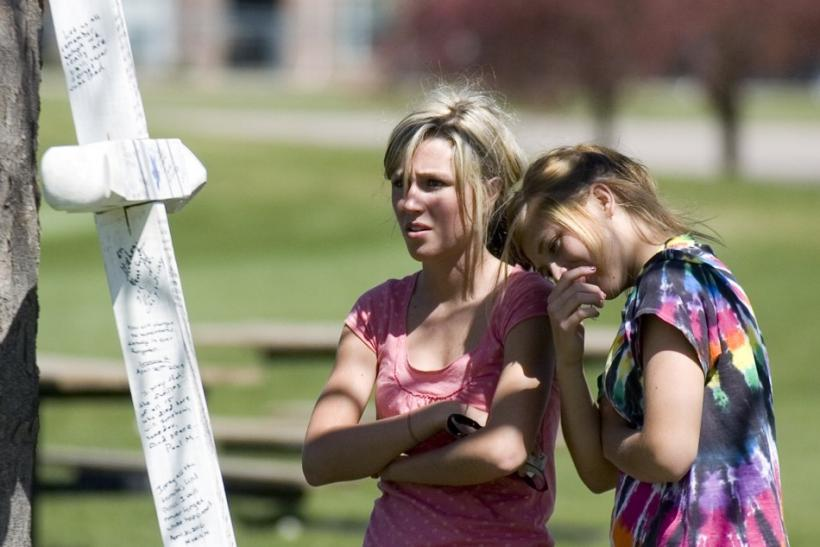 Alyssa Nikolas and Kailey Bucher read messages written to victims of the 1999 shooting at Columbine High School in Clement Park in Littleton