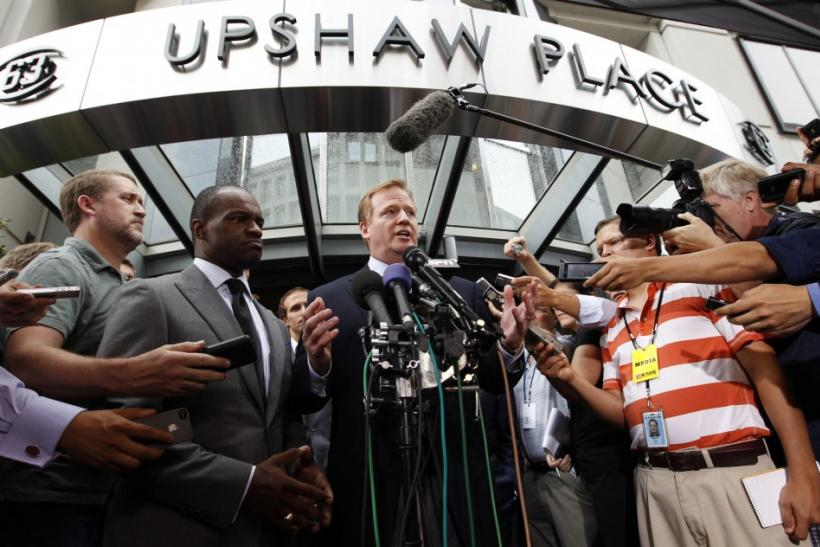 Executive director of the NFL Players Association Smith and NFL Commissioner Goodell speak outside the NFL Players Association Headquarters in Washington