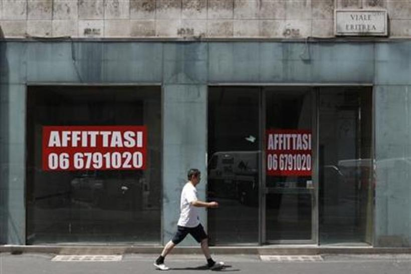 "A man walks past a shop with signs reading, ""for rent"" in downtown Rome"