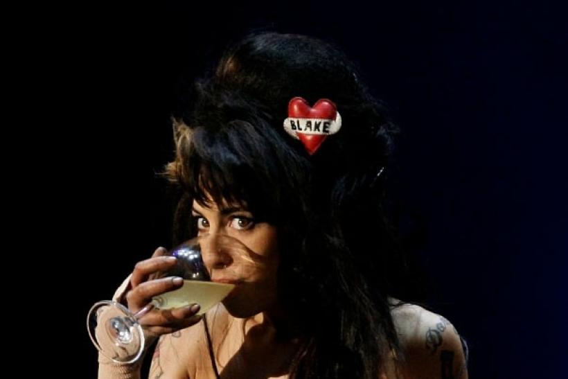 "British singer Amy Winehouse drinks while performing during the ""Rock in Rio"" music festival in Lisbon May 30, 2008"