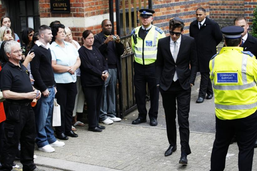 Music producer Mark Ronson (C) walks past members of the public as he leaves Golders Green Crematorium after the funeral of British singer Amy Winehouse, in north London
