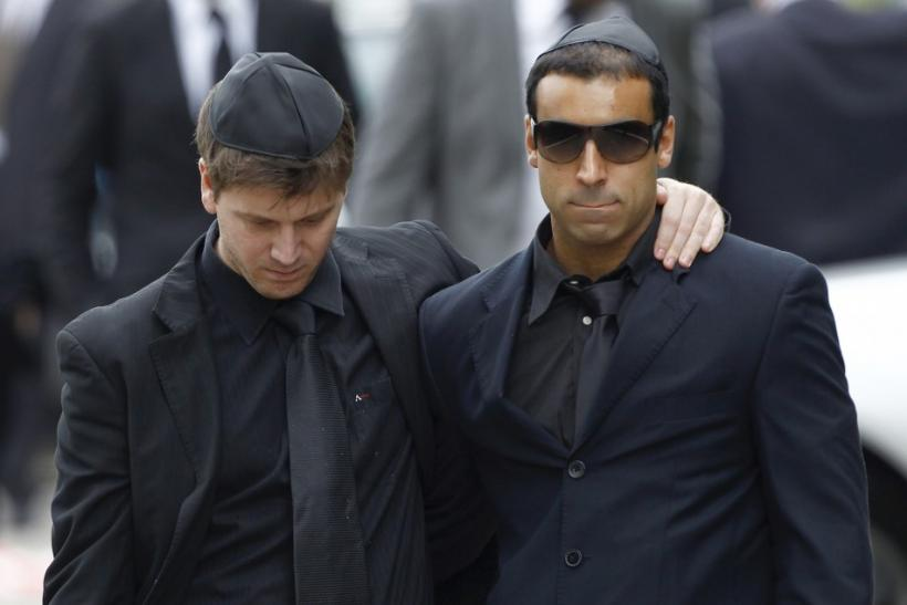 Mourners embrace as they leave the funeral service for Amy Winehouse at a cemetery in north London