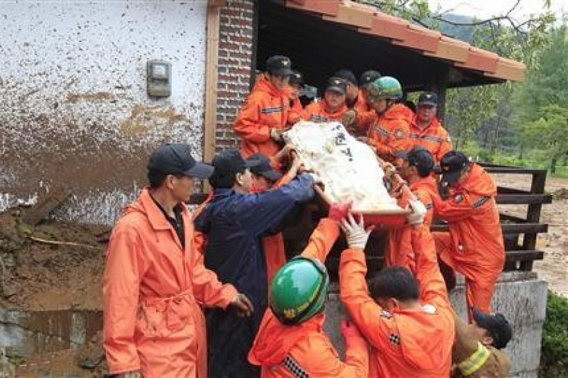 Rescue workers remove a body from a house following a landslide in Chuncheon, about 100 km (60 miles) east of Seoul, July 27, 2011. A landslide caused by torrential rain crashed into a South Korean mountain resort east of Seoul early on Wednesday, destroy