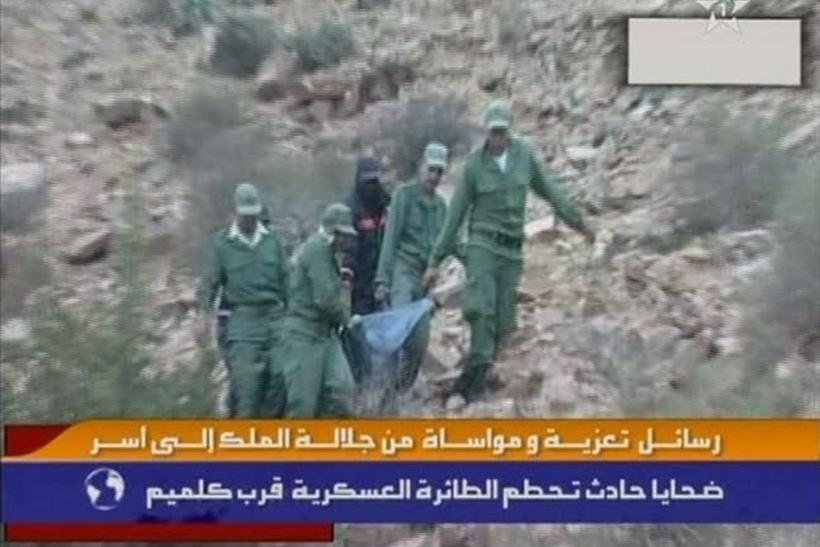 Still image from video shows rescue workers carrying the body of a victim from the wreckage of an aircraft after it crashed while trying to land in Guelmim
