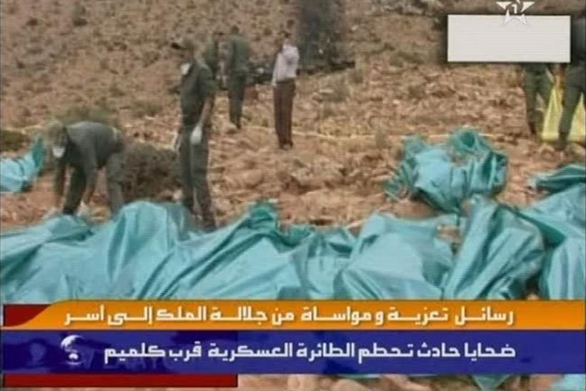 Still image from video shows rescue workers standing among bodies of victims after an aircraft crashed while trying to land in Guelmim
