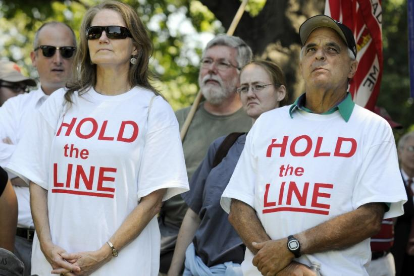 "Tea Party supporters wear ""Hold the Line"" t-shirts as dozens rallied near the U.S. Capitol against raising the debt limit in Washington"