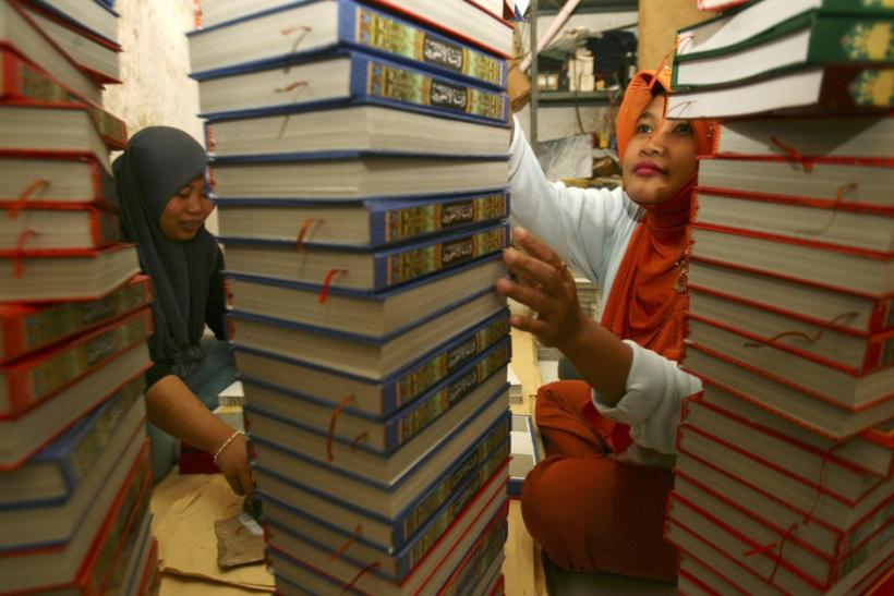 Workers count of printed copes of the Koran at a printing press near Sunan Ampel mosque in Surabaya, Indonesia East Java province
