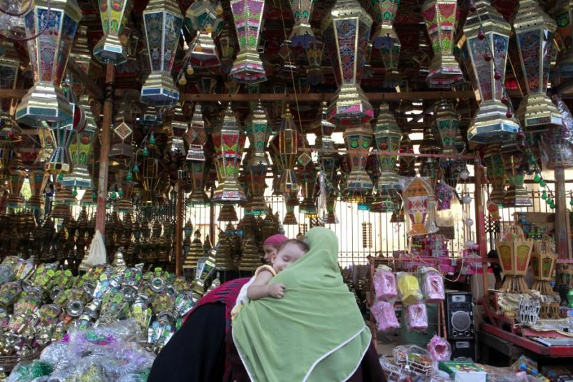 A woman carrying her child buys Ramadan lanterns in a shop in Cairo ahead of the Muslim fasting month of Ramadan