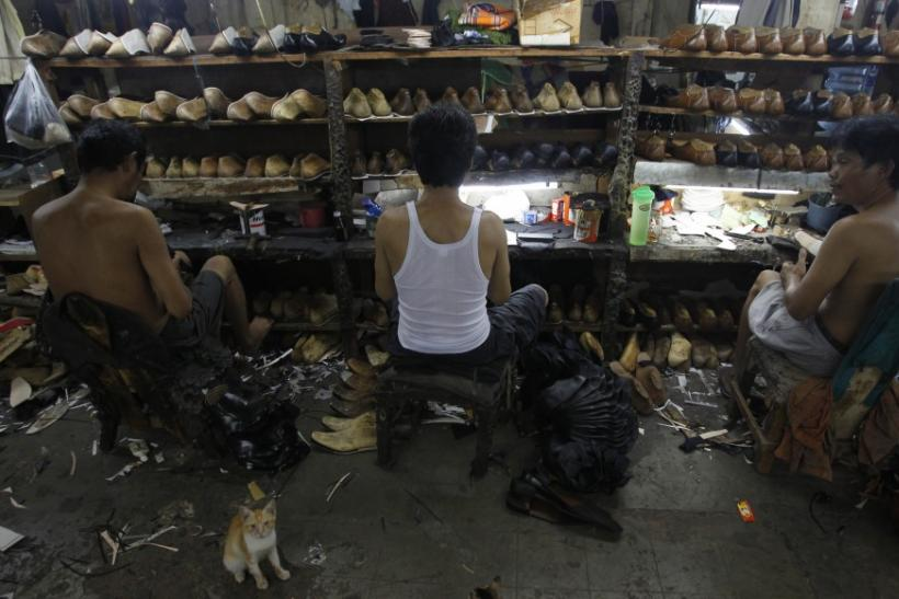 Workers make leather shoes at a family-run factory in Jakarta