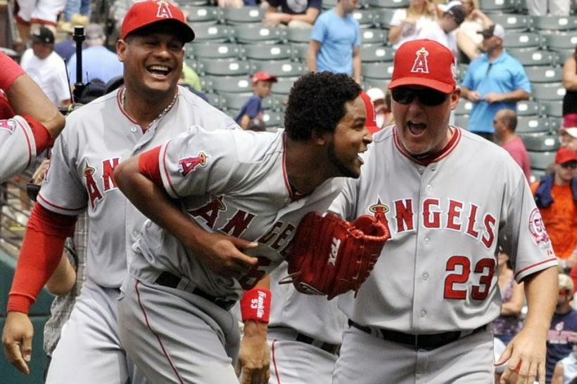 Los Angeles Angels' pitcher Ervin Santana (C) celebrates with pitching coach Mike Butcher (23) and Bobby Abreu (L) after throwing a no hitter during the MLB American League baseball game against the Cleveland Indians in Cleveland, Ohio July 27, 2011.