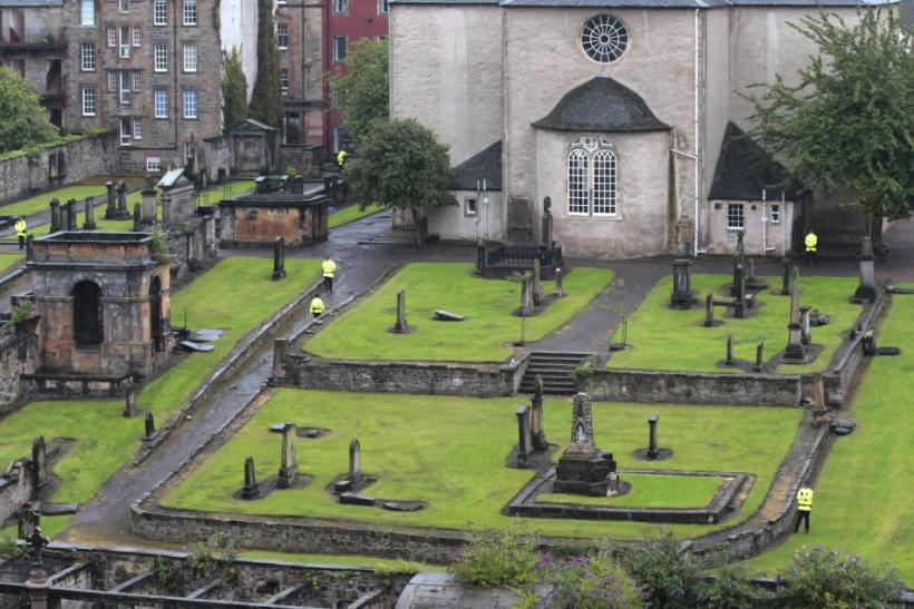 Police stand guard in the church graveyard as preparations begin for the wedding of Zara Phillips and Mike Tindall inside the Canonngate Kirk in Edinburgh, Scotland July 28, 2011. The Queen's grandaughter Phillips will marry England rugby player Tindall a