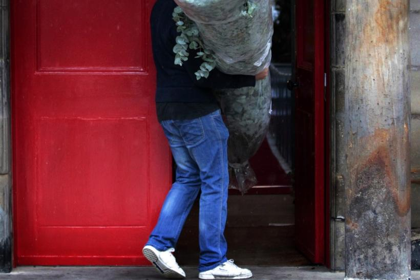 A man carries a floral decoration as preparations begin for the wedding of Zara Phillips and Mike Tindall, inside the Canonngate Kirk in Edinburgh, Scotland