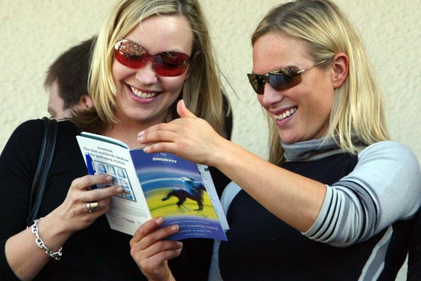 Britain's Zara Phillips (R) studies the race card with an unidentified friend before the first race at the Cheltenham National Hunt Festival meeting in southern England
