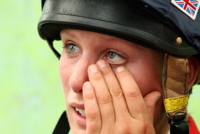 Britain's Zara Phillips speaks with British team officials and team-mates after finishing her round in the show-jumping portion of the Eventing competition at the World Equestrian Games in Aachen
