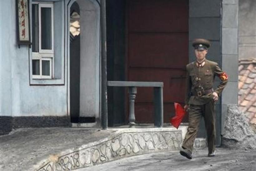 A North Korean soldier holds a red flag as he walks on the banks of Yalu River near the North Korean town of Sinuiju, opposite the Chinese border city of Dandong