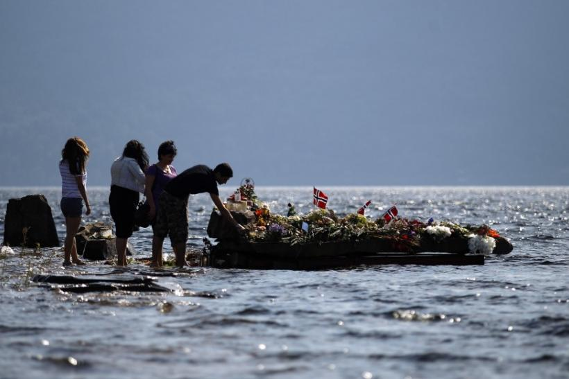 People offer flowers on a memorial stone in Tyrifjorden lake near Utoeya island