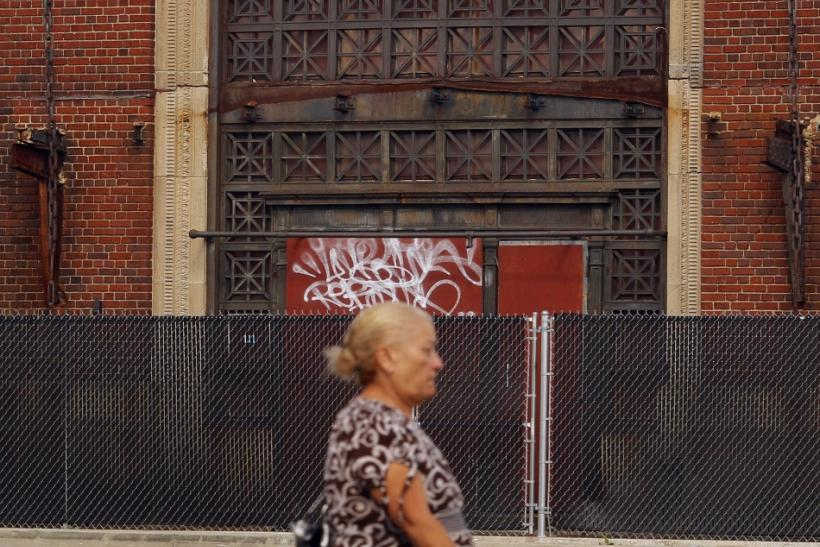 A woman passes the unused and boarded-up Pawtucket-Central Falls train station in Central Falls