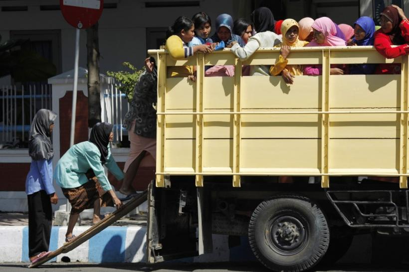 Indonesian Muslim women climb up a truck on a make-shift ladder on the way for prayers in Bojonegoro