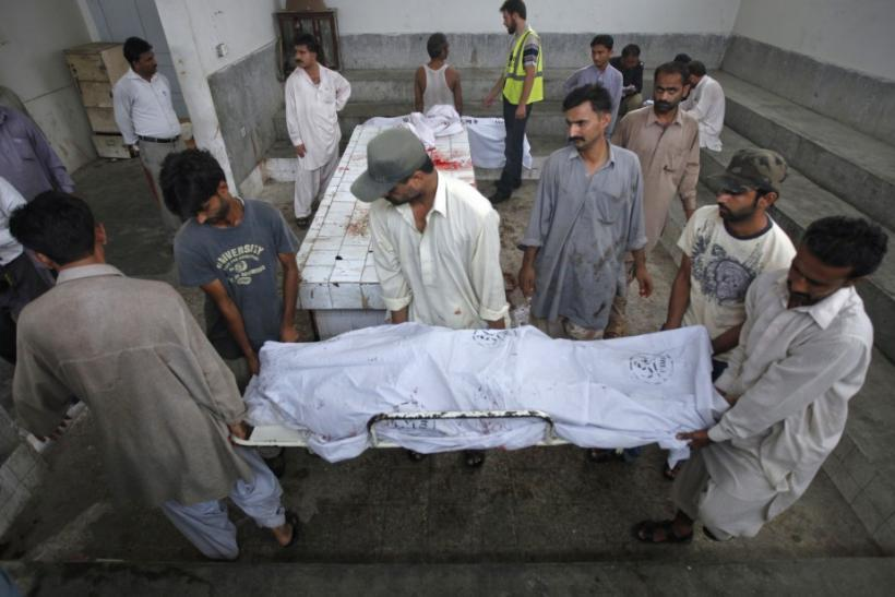 Family members move the body of a man, killed by unidentified gunmen during a shoot out, from morgue in Karachi