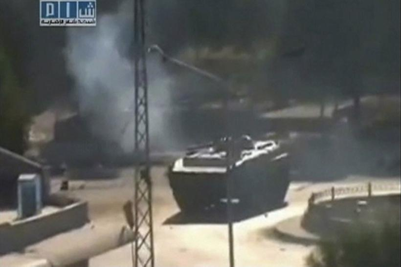Smoke is seen near a tank at Al-Bahra roundabout in Hama in this still image taken from video