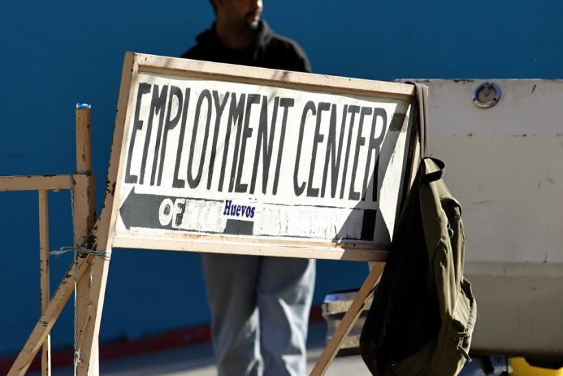 A day labourer stands behind a sign for an employment center in San Diego