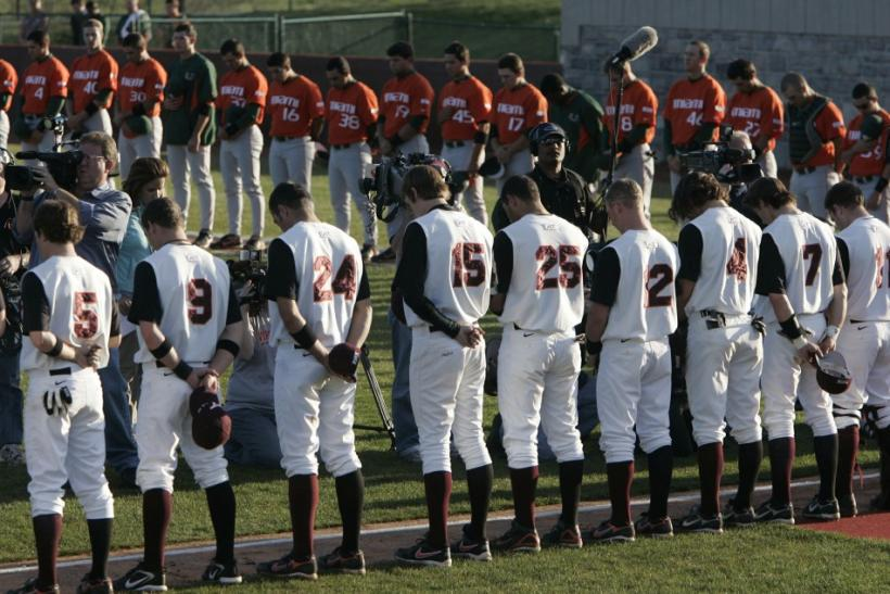 The Virginia Tech baseball team bow their heads during a 32-second moment of silence in Blacksburg