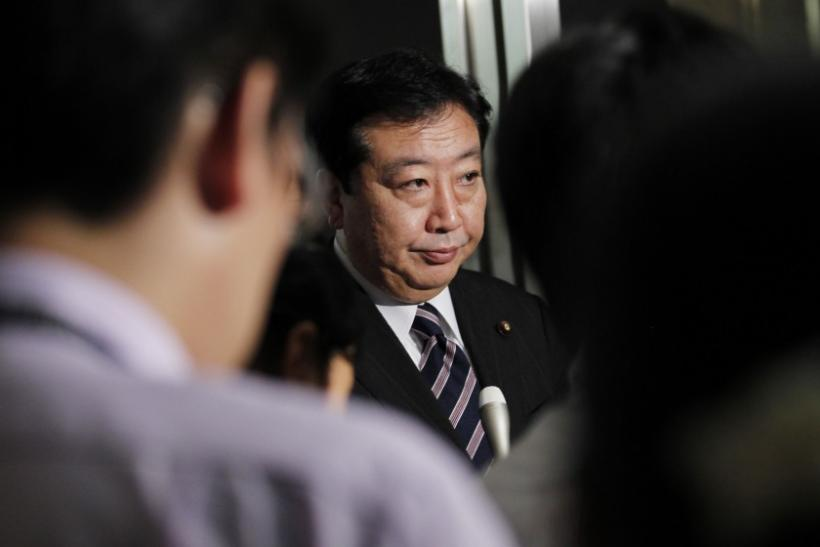 Finance Minister Yoshihiko Noda is surrounded by reporters in Tokyo