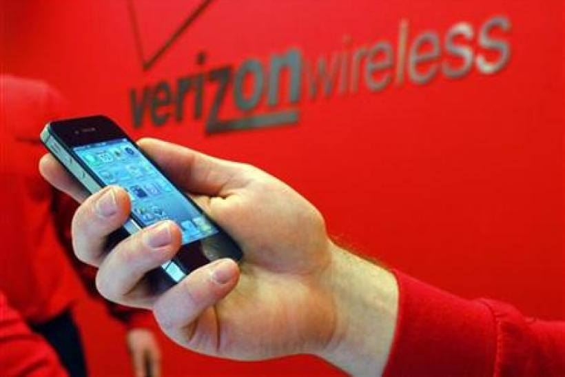 Employee holds out an iPhone for a customer at a Verizon store in Boston