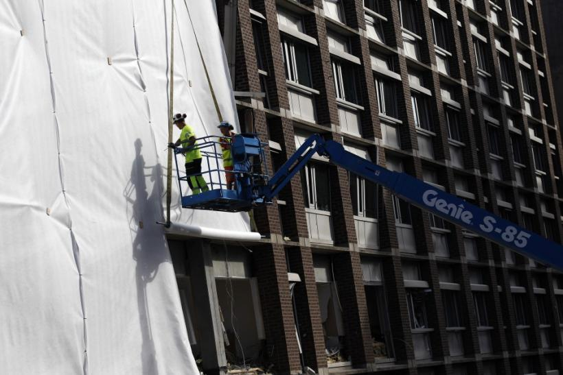 Workers cover the facade of a building that forms part of the government complex damaged by the July 22 bomb attack, in Oslo