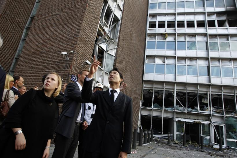 Germany's Vice-Chancellor and Economy Minister Philipp Roesler (R) gestures in front of the entrance of a building that forms part of the government complex damaged by the July 22 bomb attack, in Oslo