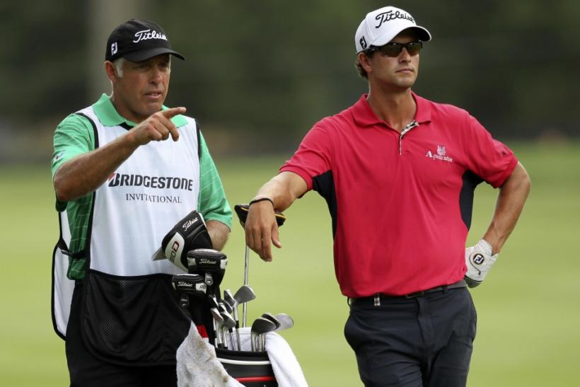 Australia's Adam Scott listens to his caddie, Steve Williams, on the 13th fairway during the first round of the WGC Bridgestone Invitational PGA golf tournament at Firestone Country Club in Akron