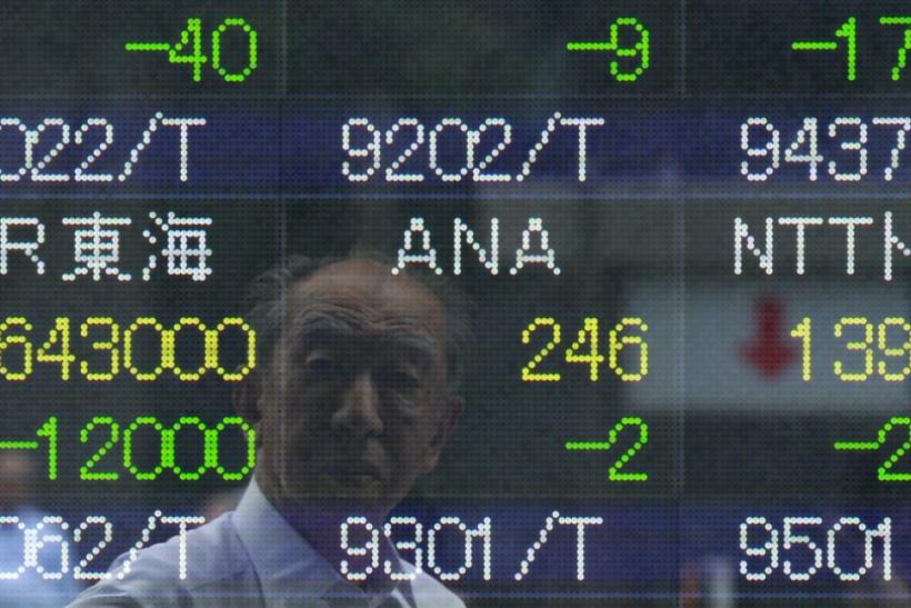 A man's reflection is seen on an electronic stock quotation board outside a brokerage in Tokyo