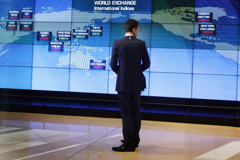A television journalist looks at a display board shortly after the local market opened at the Australian Stock Exchange in Sydney