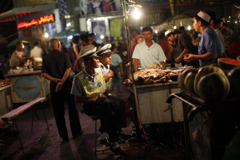 Police officers eat at an Uighur ethnic market area in Kashgar