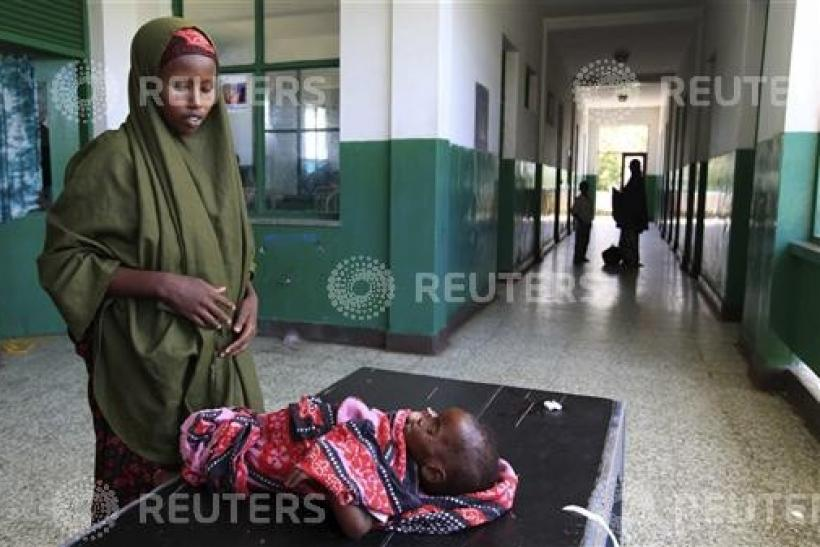 Somali woman attends to her malnourished child along corridor of paediatric ward at Banadir hospital in southern Mogadishu