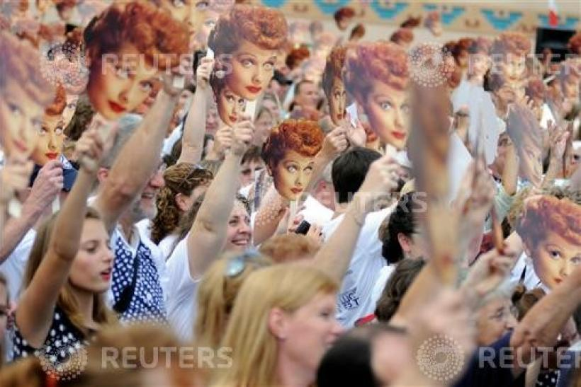 People hold up masks of Lucy Ball during attempt to set a new Guinness world record for most Lucy Ricardo lookalikes assembled in one place, in Jamestown