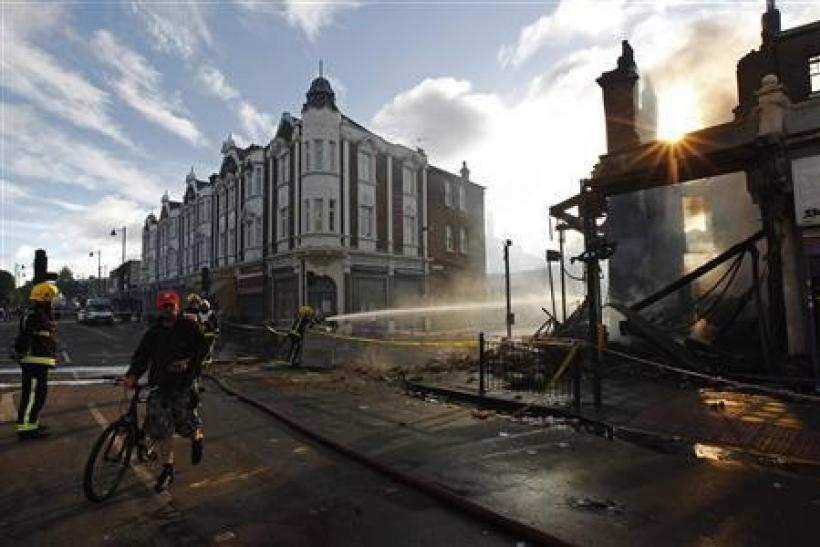 A cyclist passes firemen dowsing down buildings set alight during riots in Tottenham, north London