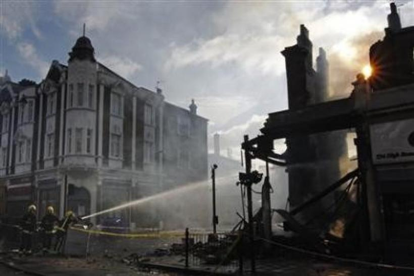 Firemen dowse down buildings set alight during riots in Tottenham, north London, August 7, 2011. Rioters throwing petrol bombs battled police in a economically deprived district of London overnight, setting patrol cars, buildings and a double-decker bus o