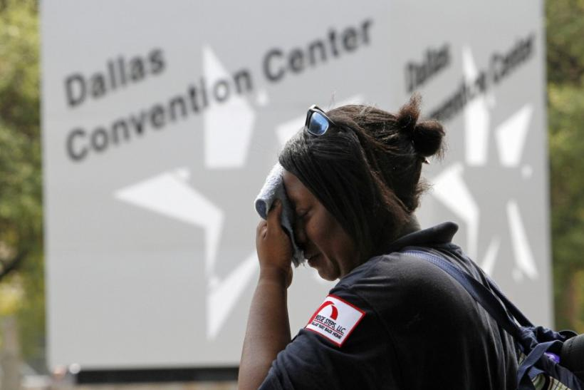 Tamika Davis wipes her face while waiting for a bus in Dallas